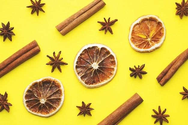 Fond de noël d'oranges séchées, anis étoilé et cannelle. fond jaune pose à plat