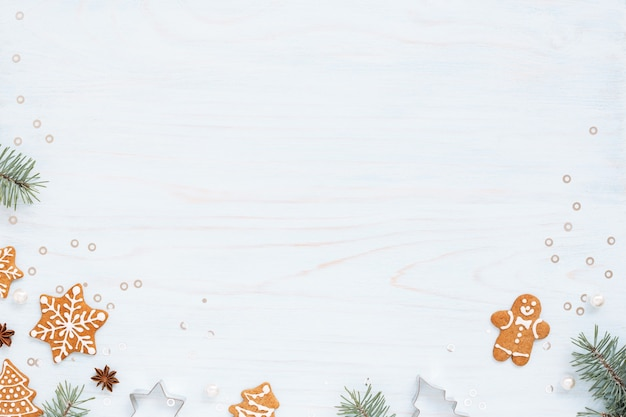 Fond de noël avec pains d'épices, sapin et décorations sur table bleu clair