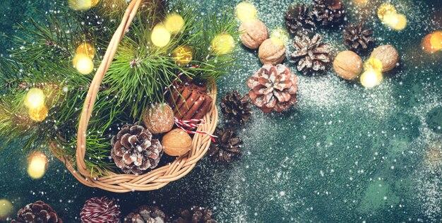 Fond de noël. panier avec pommes et branches de sapin, noix et cannelle. format de bannière