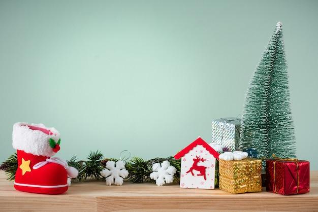 Fond de noël. un petit arbre de noël et des boîtes avec des cadeaux sur une table en bois. fond vert. espace pour le texte.