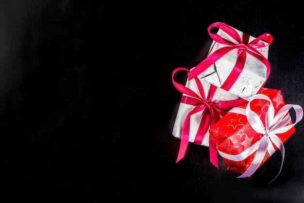 Fond de noël pour carte de voeux, avec une branche d'arbre de noël et des boîtes de cadeaux avec des rubans, sur l'espace de copie vue de dessus fond noir pour le texte