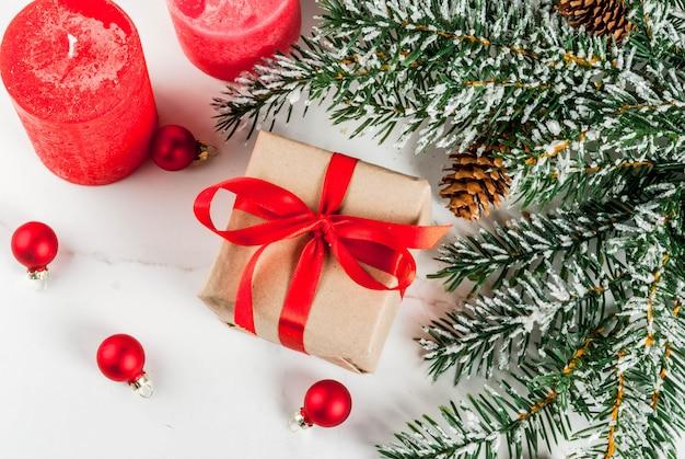 Fond de noël pour carte de voeux. branches d'arbres de noël avec effet neige avec ruban rouge festif, pommes de pin, coffrets cadeaux et bougies, sur fond de marbre blanc vue de dessus