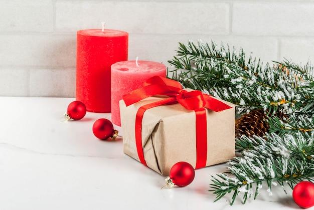 Fond de noël pour carte de voeux. branches d'arbres de noël avec effet neige avec ruban rouge festif, pommes de pin, coffrets cadeaux et bougies, sur fond de marbre blanc