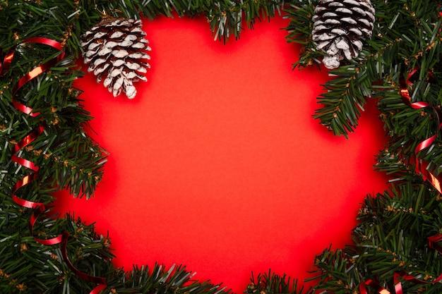Fond de noël rouge avec décoration et espace libre pour les salutations ou une liste d'invités