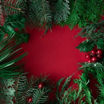 Fond de noël rouge avec décoration d'hiver, branches d'arbres et feuilles. disposition de l'espace de copie de vacances.