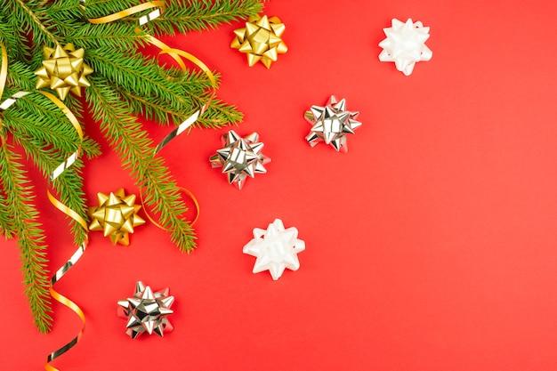Fond de noël rouge du nouvel an avec des branches d'épinette décorées. serpentine dorée, éléments décoratifs brillants. vue de dessus, copie de l'espace.