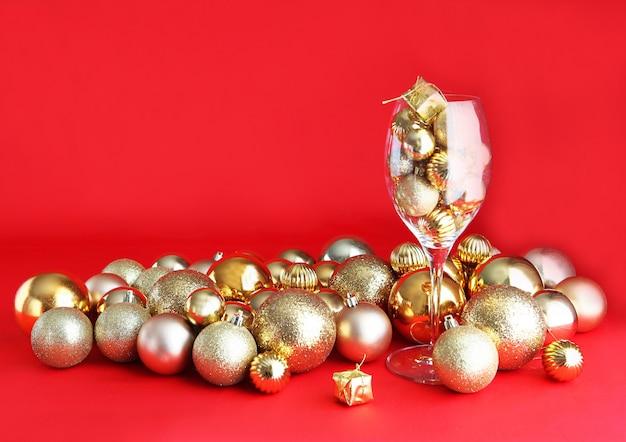 Fond de noël rouge et or avec verre de vigne et décorations de noël or à l'intérieur. verre de vigne avec décorations de noël