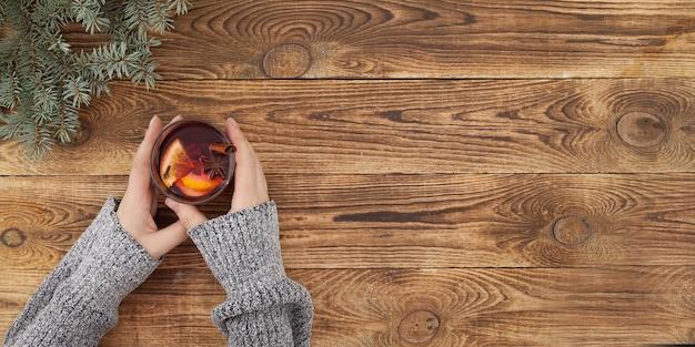 Fond de noël, vin chaud dans les mains des femmes sur une table en bois, vue du dessus