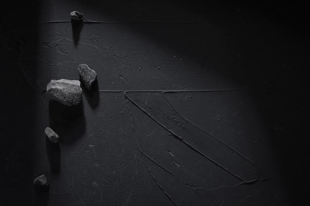 Fond noir en béton avec des pierres