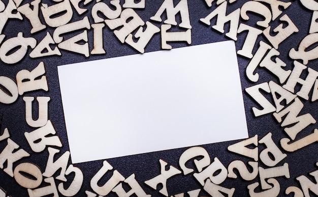 Sur un fond noir en bois lettres anglaises et une carte vierge blanche pour le texte ou l'illustration. copier l'espace
