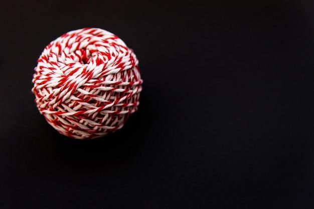 Sur fond noir, une boule de ficelle est rouge et blanche. fils pour emballer des cadeaux. décor de noël.