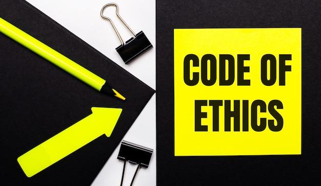 Sur un fond noir, un crayon jaune vif et une flèche et une feuille de papier jaune avec le texte code de déontologie