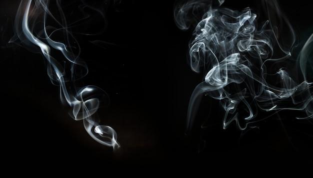 Fond noir avec deux formes ondulées de fumée