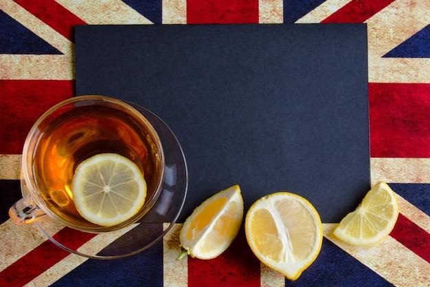 Fond noir sur le drapeau britannique avec une tasse de thé au citron