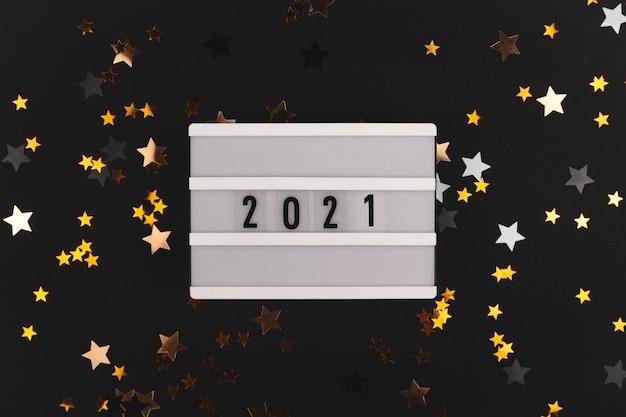 Fond noir avec des étoiles qui brillent et panneau écrit bonne année arrière-plan copie espace