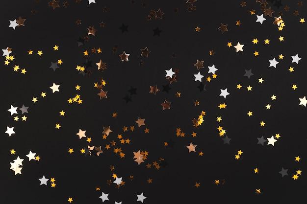 Fond noir avec des étoiles qui brillent et scintillent dans l'espace de copie de fond de bonne année jaune