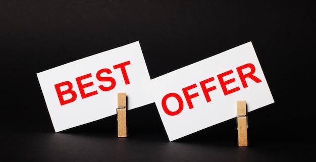 Sur un fond noir sur des pinces à linge en bois, deux cartes vierges blanches avec le texte meilleure offre