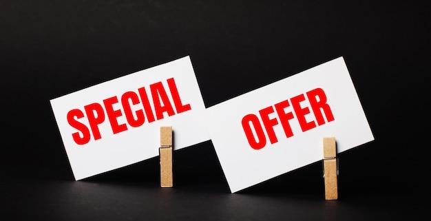 Sur un fond noir sur des pinces à linge en bois, deux cartes vierges blanches avec le texte offre spéciale