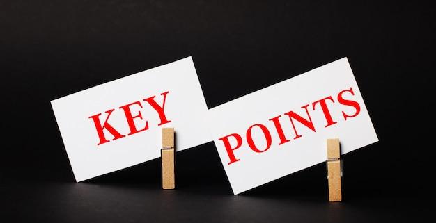 Sur fond noir sur des pinces à linge en bois, deux cartes vierges blanches avec le texte points clés