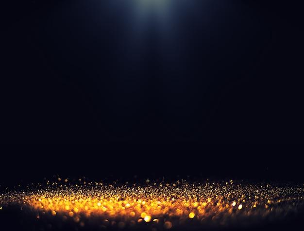 Fond noir avec des projecteurs à fond mousseux de paillettes d'or luxueuses