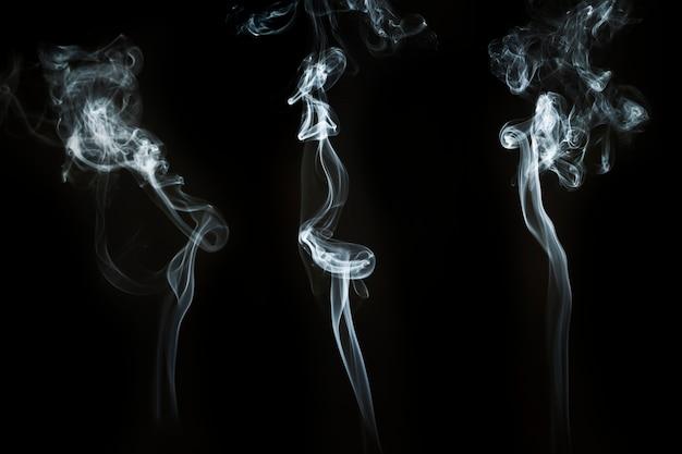Fond noir avec des silhouettes de fumée ondulée