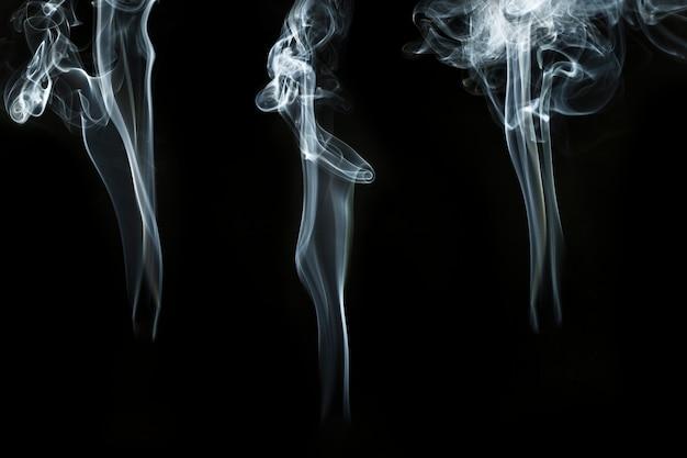 Fond Noir Avec Trois Silhouettes De Fumée Photo gratuit