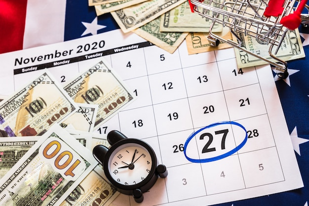 Fond noir vendredi avec panier et réveil avec jour le 27 novembre 2020 et drapeau américain.