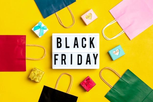 Fond noir vendredi avec des sacs d'emballage multicolores avec des boîtes-cadeaux