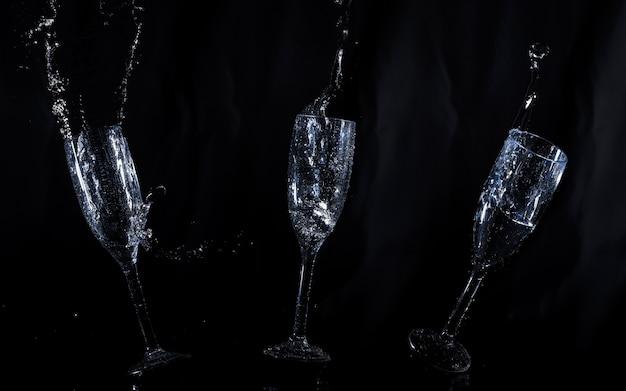 Fond noir avec des verres d'eau flottants