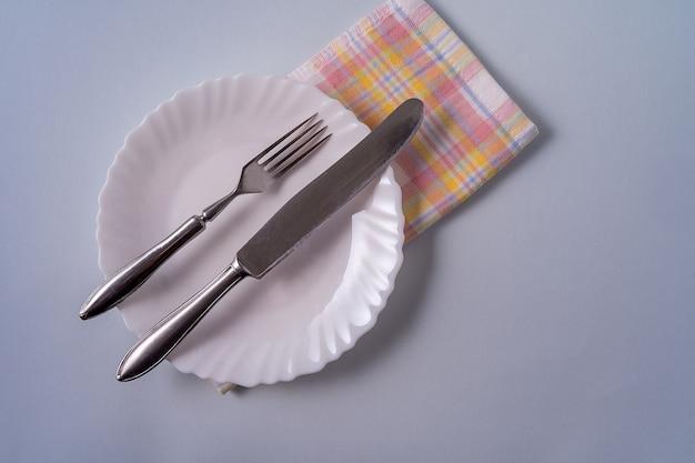 Fond de nourriture avec assiette blanche vide, couverts et serviette sur bleu