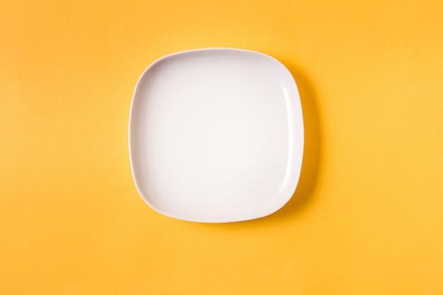 Fond de nourriture avec une assiette blanche vide sur jaune