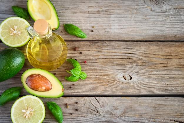 Fond de nourriture à l'avocat, citron vert, huile d'olive et basilic sur vieilles planches altérées. vue de dessus, espace pour le texte.