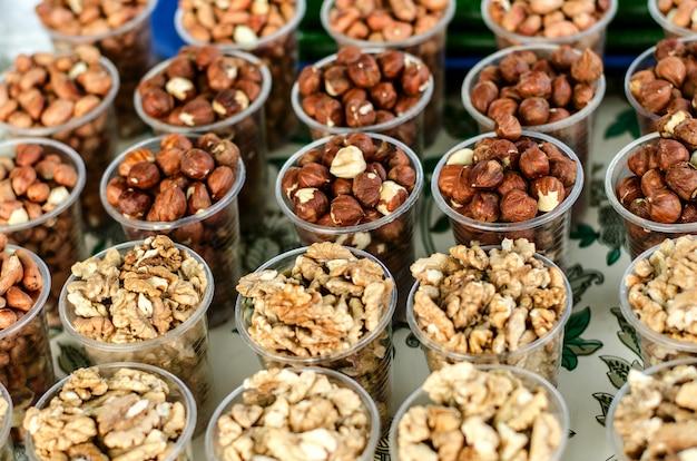 Fond de nourriture. différentes noix dans des gobelets en plastique.