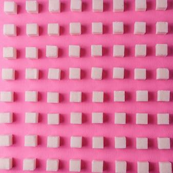 Fond de nourriture avec du sucre sur du papier de couleur rose.