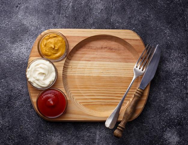 Fond de nourriture avec moutarde, ketchup, mayonnaise, fourchette et couteau. espace pour le texte