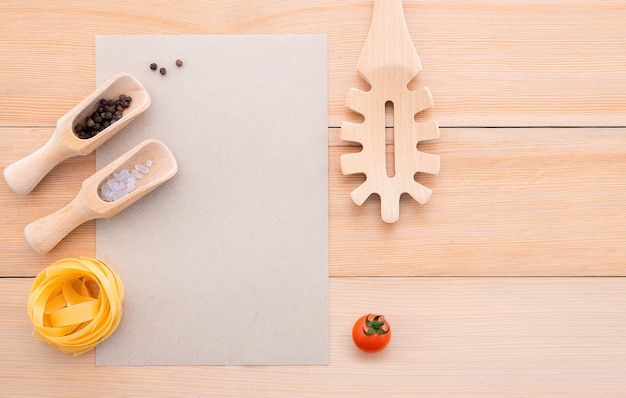 Fond de nourriture pour de savoureux plats italiens avec du papier brun vierge et une louche de pâtes vintage sur fond en bois.