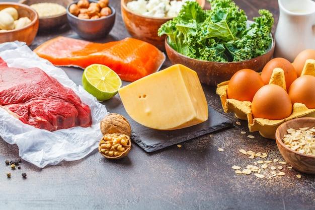 Fond de nourriture de régime équilibré. aliments protéinés: poisson, viande, fromage, quinoa, noix sur fond sombre.