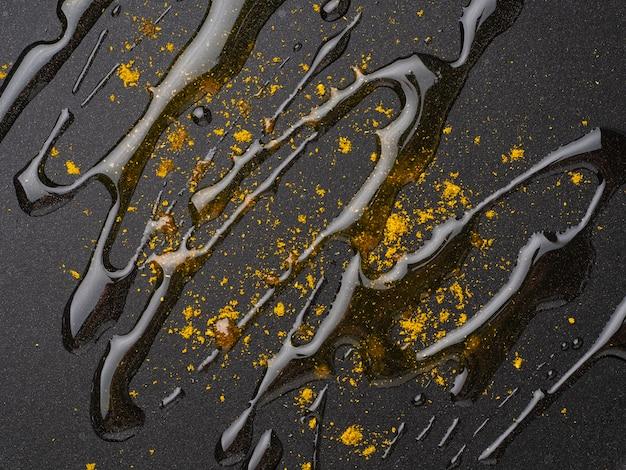 Fond de nourriture sombre avec des épices au curry, huile sur la poêle en fluoroplastique, macro, gros plan, vue de dessus