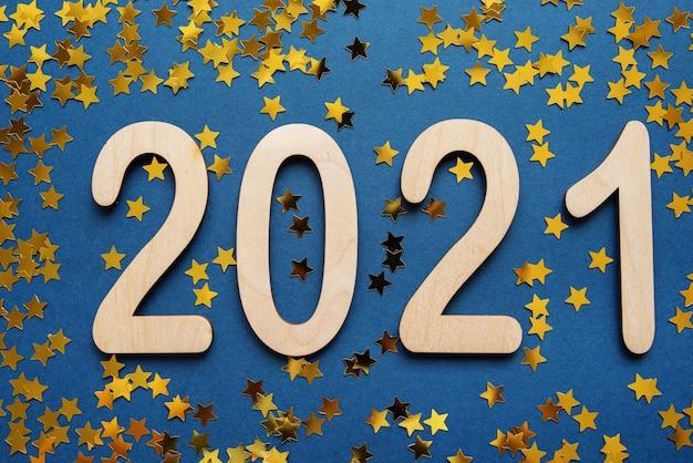 Fond de nouvel an avec des numéros 2021 sur bleu avec des étoiles dorées.