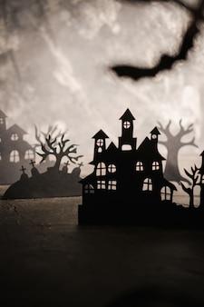 Fond de nuit d'halloween. l'art du papier. village abandonné dans une sombre forêt brumeuse