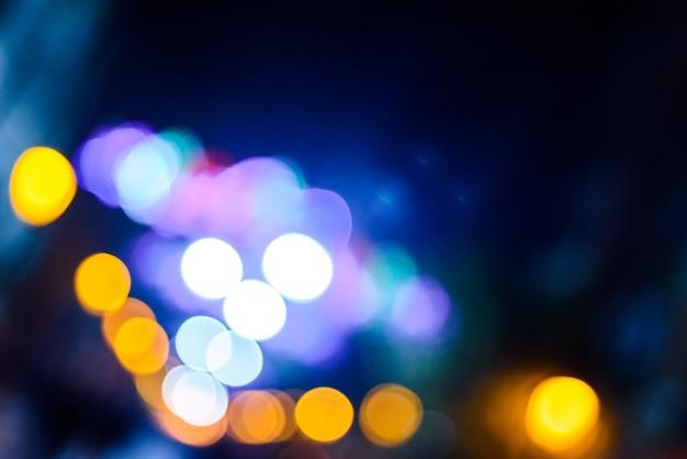 Fond de nuit urbaine défocalisé avec des cercles colorés.