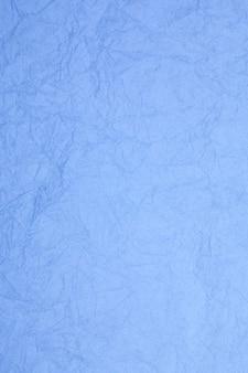 Fond obsolète texturé de papier bleu vintage froissé.