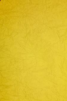 Fond obsolète texturé de papier jaune vintage froissé.