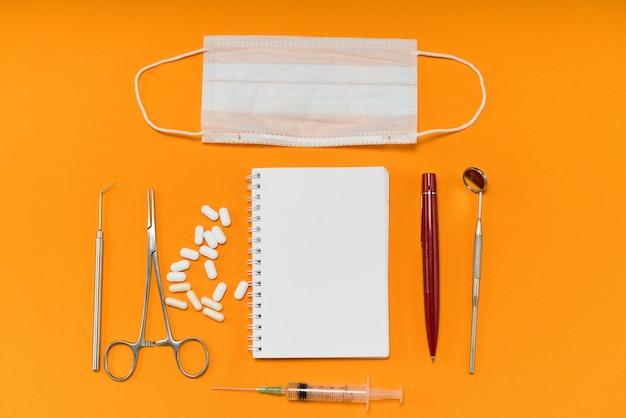 Sur un fond orange se trouvent des pilules, un cahier et des instruments dentaires