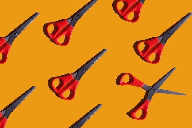 Fond orange vif avec des ciseaux rouges motif sur le thème du travail manuel et fait main