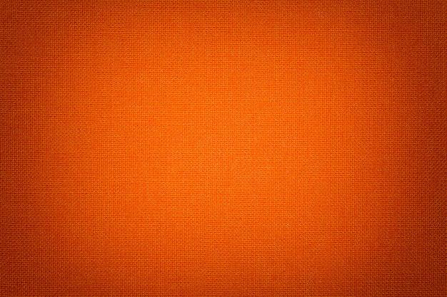 Fond orange vif d'une matière textile avec motif en osier, gros plan.
