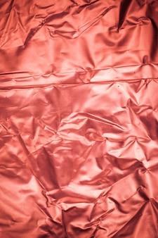 Fond de papier d'aluminium rouge froissé.