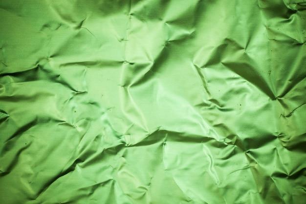 Fond de papier d'aluminium vert froissé.