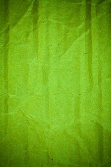 Fond de papier cartonné vert froissé texturé.