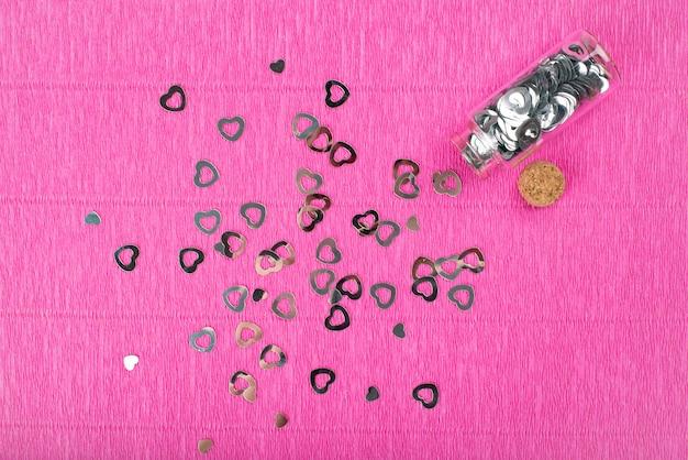 Fond de papier crépon rose vif avec des paillettes de coeurs.